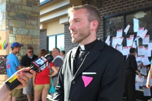 The Rev. Benjamin Hutchison discusses with the media what he says was a forced resignation from Cassopolis United Methodist Church after church leaders asked about his same-sex partner, on Tuesday, July 28, 2015 in  Lansing, Mich. United Methodist clergy and churchgoers held a news conference outside the bishop's office in support of Hutchison, an openly gay pastor who says he was forced to resign. Advocates taped a pledge to the office door asking for LGBT inclusiveness in the church, which accepts gay members but not openly gay pastors. (Emily Lawler/The Grand Rapids Press, MLive.com via AP)