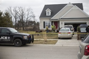 In this Sunday, Feb. 21, 2016 photo, Genesee County Sheriff's and Fenton Township police wait outside of a home in the Stony Brook subdivision of Fenton, Mich. The sheriff's office said a family of six, including four children, have died from possible carbon monoxide poisoning. (Conor Ralph/The Flint Journal - MLive.com via AP)